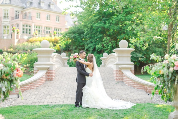 bride in vera wang lindsey dress and vera wang veil, groom in armani suit, arms around each other