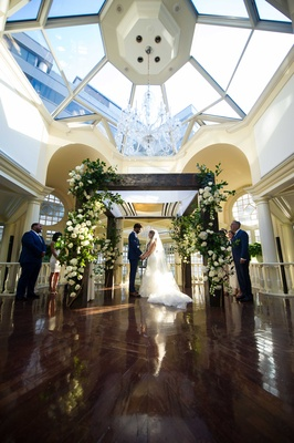 a couple weds in traditional jewish ceremony under wooden chuppah with white florals and greenery