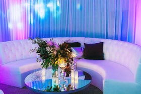 Wedding reception white lounge furniture mirror coffee table flower arrangement bright lighting