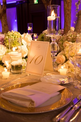 Wedding reception table number with monogram, glittery gold border, candles, green hydrangeas, white