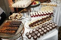Glass platters of chocolate strawberries and cupcakes