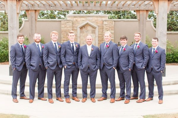 groom and groomsmen in navy suits brown dress shoes pink flower boutonnieres
