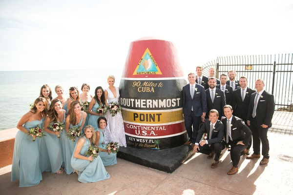 Bridesmaids in blue dresses and groomsmen with the conch republic marker 90 miles to cuba sign