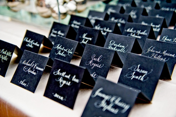 White calligraphy lettering on ebony seating cards