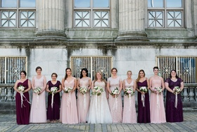 Brides in mismatched gowns in shades of blush and burgundy oxblood holding matching bouquets