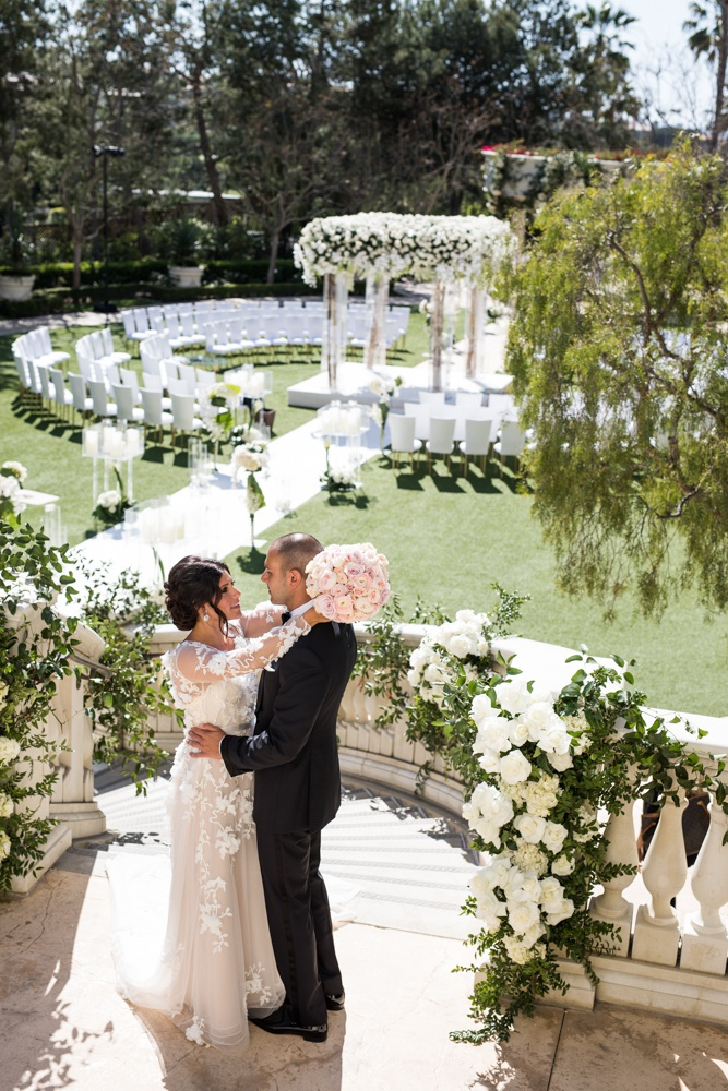 Wedding ceremony with bride and groom on top of staircase guests in the round white chairs flowers