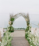 Branch wedding arch in front of ocean with wood aisle runner