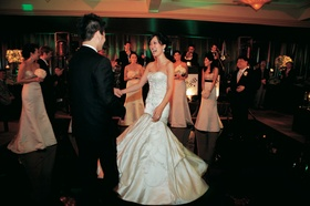 Bride in a fit-and-flare Lazaro gown and groom in a black tuxedo on the dance floor