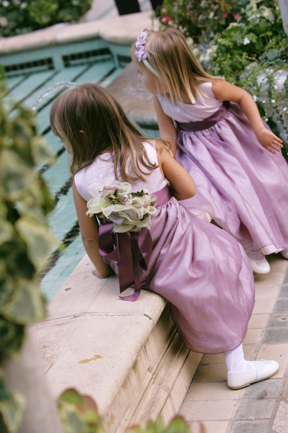 Flower girls wearing light purple dresses with dark purple sashes
