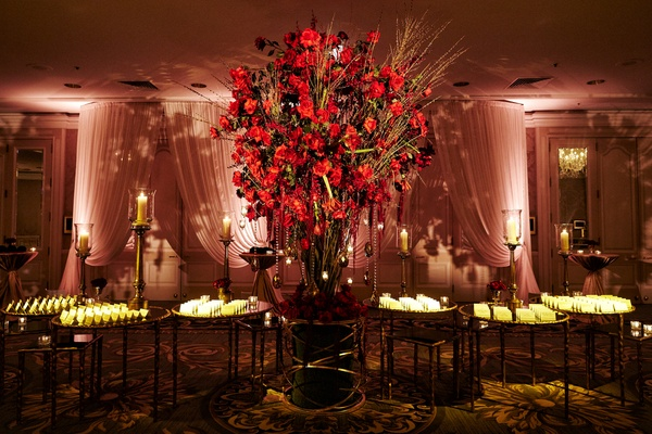 large arrangement of red roses among tables of escort card displays