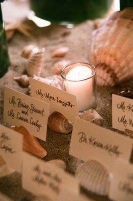 Candlelit place cards on top of sea shells
