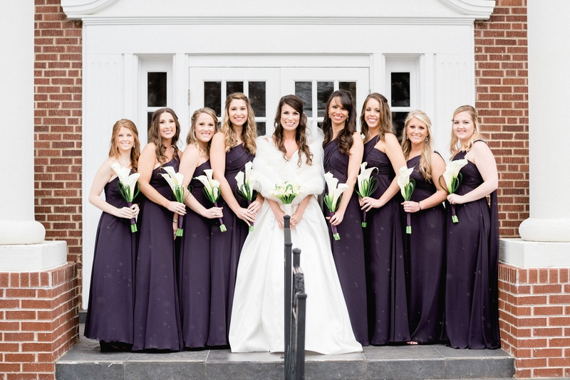 Bride in ball gown and fur wrap stole with bridesmaids in dark purple bridesmaid dresses calla lily
