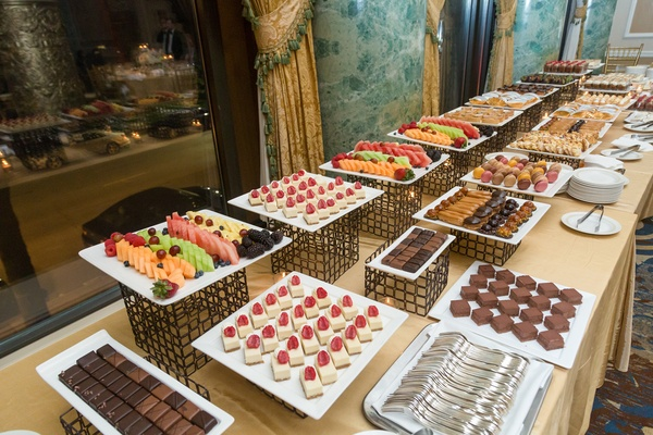 dessert table at wedding with fruits, chocolates, and pastries