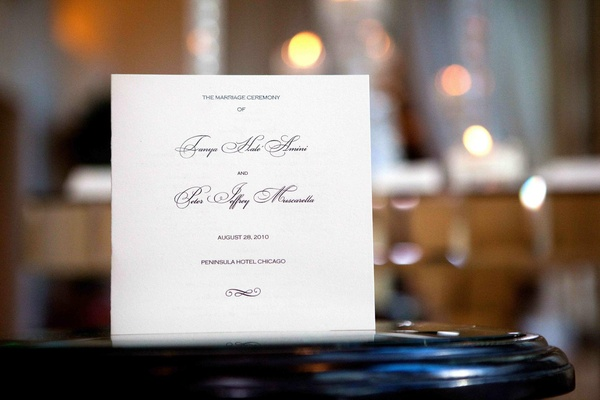 White and black ceremony booklet on table