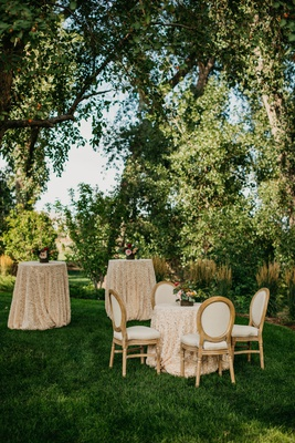 wedding reception garden setting cocktail table small bistro table with french upholstered chairs