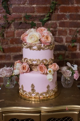 two-tier wedding cake with pink buttercream, gold details, fresh flowers