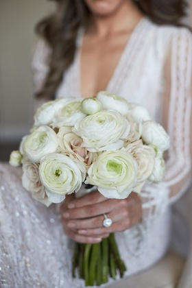 Bride in Inbal Dror wedding dress with ivory ranunculus blossoms and light pale pink roses