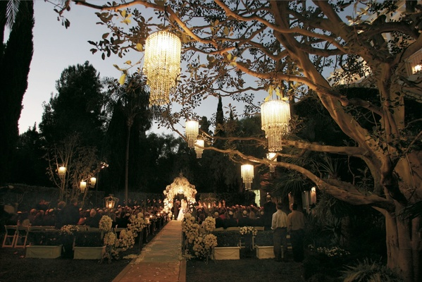 Garden ceremony with chandeliers suspended from trees and flower covered gazebo