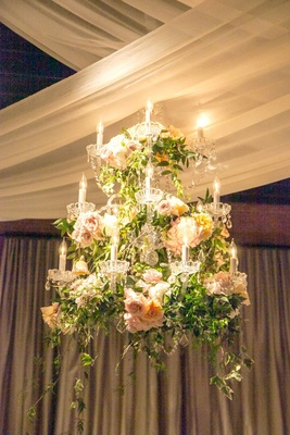 a hanging chandelier bedecked with greenery and white blush and orange flowers