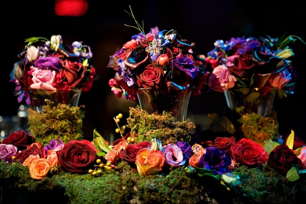 brass vases covered in moss topped with jewel toned flowers