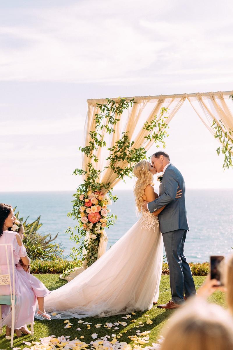 bride in custom trish peng wedding dress groom grey suit kiss ocean view ceremony pastel decor