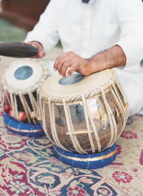 Musician plays Indian Tabla drums for an outdoor wedding ceremony