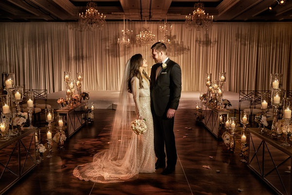 Bride in Inbal Dror wedding dress with groom in ceremony ballroom drapery chandeliers mirrors candle