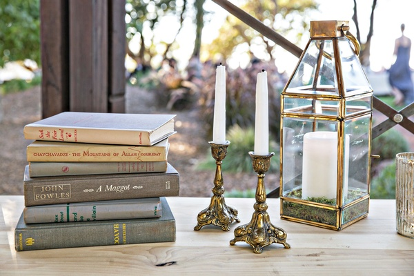 Wedding reception decor vintage inspired old books with gold candlesticks lantern candles