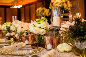 wedding reception table gold beaded charger rose gold candle votives white rose ranunculus acrylic