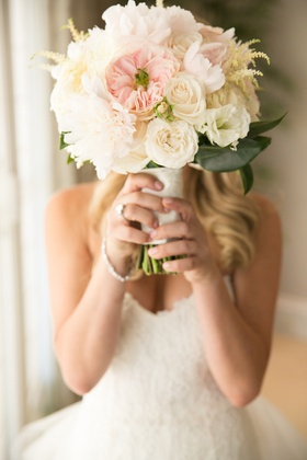 Bride hiding her face with rose blooms and peonies