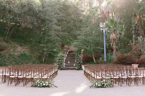wedding ceremony venue wood chairs greenery white flowers outdoor ceremony sycamore and oak trees