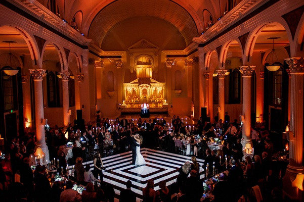 Red orange lighting at vibiana as bride and groom dance on white and black dance floor diamond