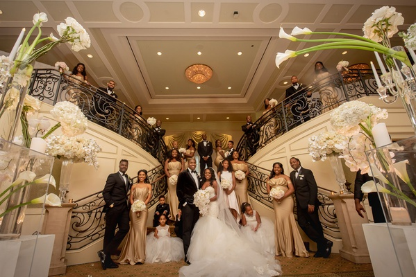 wedding party portrait by grand staircase white hydrangea calla lily gold bridesmaid dresses tuxedos