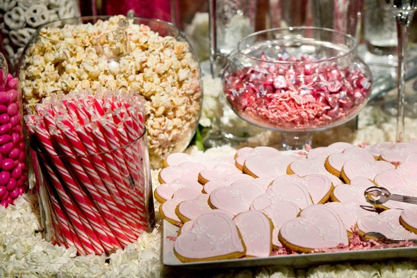 Glass bowls filled with popcorn, candies, and cookies