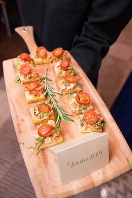 Wood cutting board server with bite size lobster BLT flatbread crostini appetizer wedding