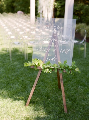 lucite ceremony sign with garland of greenery on wooden easel, cell-phone free wedding