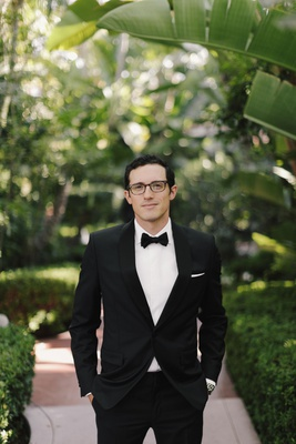 groom in tuxedo and glasses tuxedo white pocket square hands in pockets beverly hills hotel