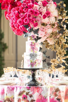 white cake with pink flower design and black jewels black butterflies pink floral linen centerpiece