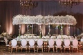 Wedding reception white chairs baby's breath overhead centerpiece white flowers