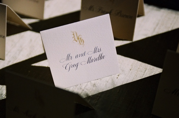 Place card with a golden Old English monogram and script font