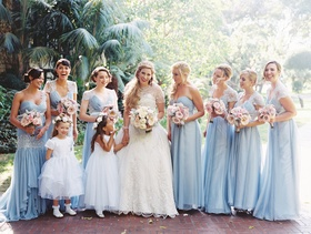 Bride in Eve of Milady with bridesmaids in blue dresses mismatched two flower girls in white