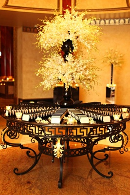 Wedding place card table with white flowers in black vases and black and white place cards
