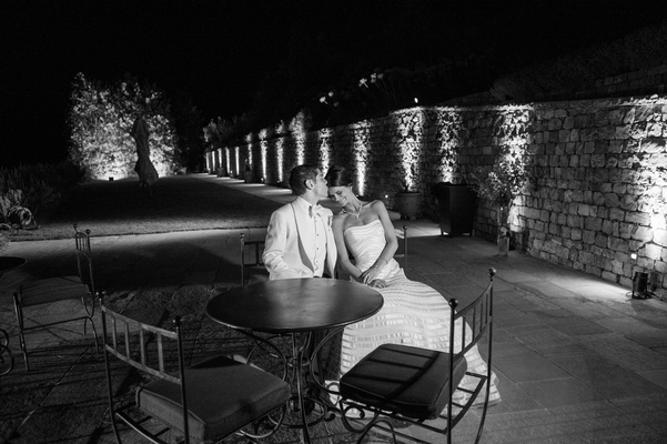 Black and white photo of groom kissing bride in a strapless Vera Wang gown