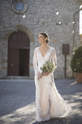 bride in inbal dror lace wrap dress with v neck and long sleeves in tuscany courtyard