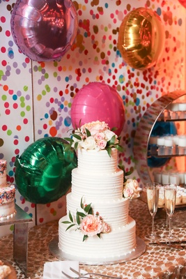 Four layer wedding cake with fresh blush flowers on dessert table with helium balloons confetti