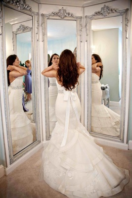 Bride in three way mirror with ivory tiered wedding dress