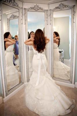 Bride in three way mirror with ivory tiered wedding dress