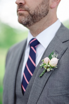 boutonniere with flower buds, grey suit, and navy tie with pink stripes