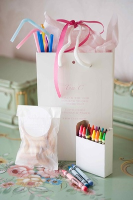 White gift bag filled with straws and crayons