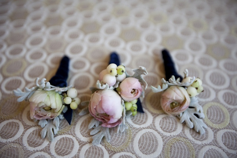 Floral boutonnieres wrapped in dark blue ribbon